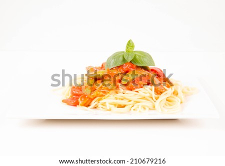 Spaghetti with pea and bacon sauce, decorated with basil - stock photo