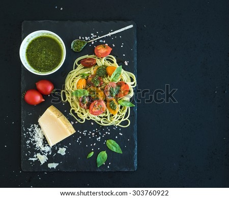 Spaghetti with pesto sauce, roasted cherry-tomatoes, fresh basil and parmesan cheese on black stone serving board over dark grunge backdrop. Top view, copy space - stock photo