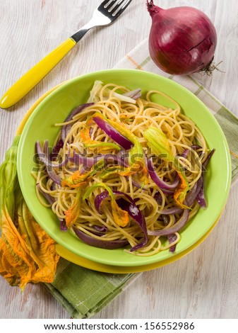 spaghetti with pumpkin flowers and onions - stock photo