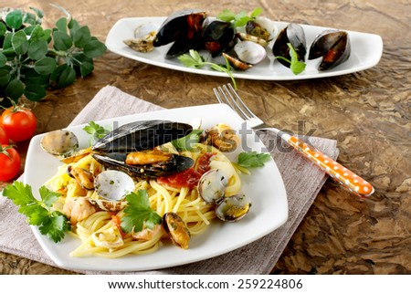 Spaghetti with salmon, clams and mussels on complex background - stock photo