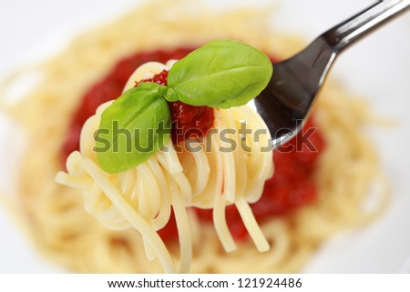 Spaghetti with tomato sauce and basil on a fork