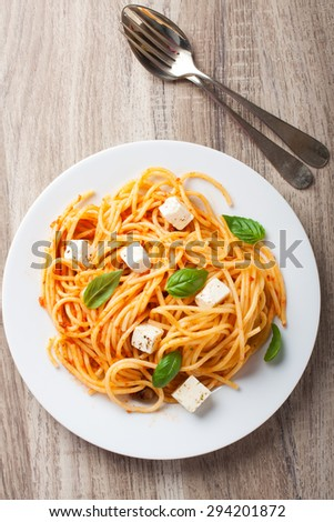 Spaghetti with tomato sauce, feta cheese and basil leaves on white plate on wooden background. Italian healthy food background. View from above. - stock photo