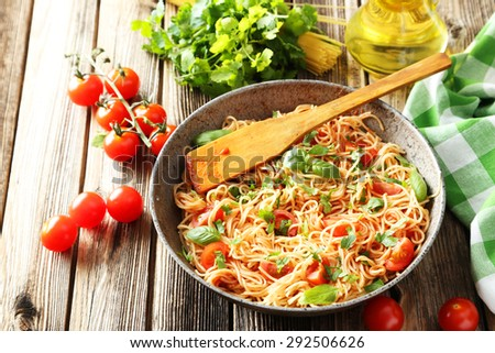 Spaghetti with tomatoes and basil on brown wooden background - stock photo