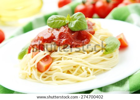 Spaghetti with tomatoes and basil on plate on white wooden background - stock photo