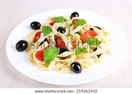 Spaghetti with tomatoes, basil and olives on plate on table