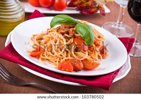 Spaghetti with tuna, cherry tomatoes and capers. - stock photo