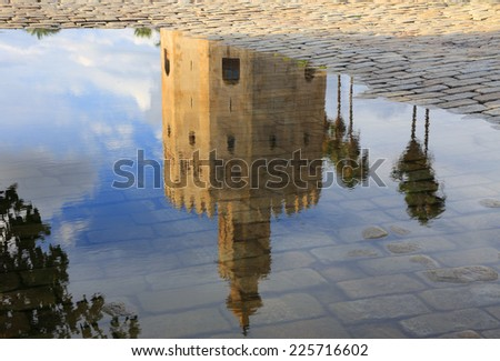 Spain,Andalusia,Seville. The Torre del Oro - Golden Tower reflected in a puddle on a cobblestone pavement. - stock photo