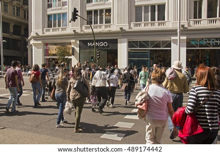Spain,Madrid - May 27, 2016: People crossing the road while shopping in the Gran Via main street in Madrid, Spain on May 27, 2016