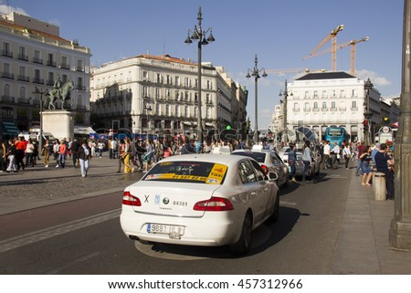 Spain,Madrid - May 27, 2016: Taxi cabs and people walking in the Puerta del Sol square in Madrid, Spain on May 27, 2016 - stock photo