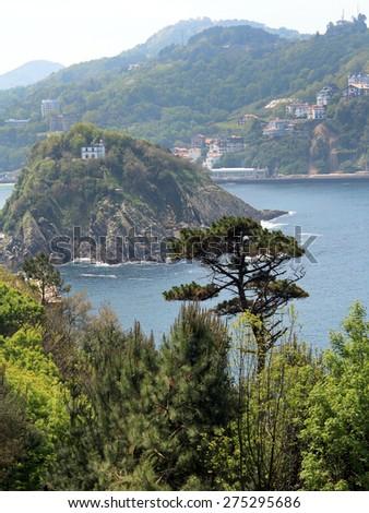 Spain, San Sebastian. View of the island Santa Klara, located in the center of the Gulf of La Concha. - stock photo