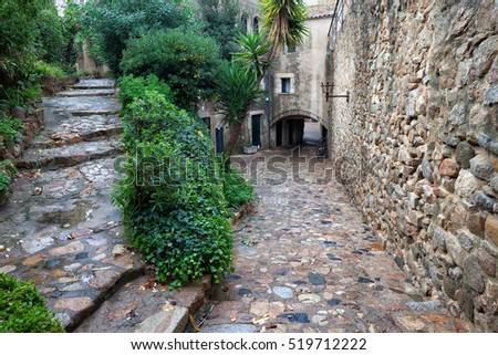 Spain, Tossa de Mar, cobbled street, staircase and stone wall in medieval Old Town - Vila Vella