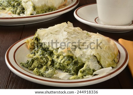 Spanakopita, spinach and kale with feta and ricotta cheeses wrapped in flaky phyllo pastry - stock photo