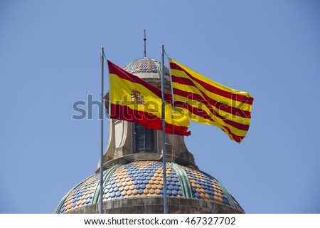 Spanish and Catalan flag flying together against blue sky on a bank building in Barcelona, Spain