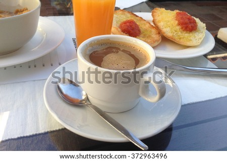 Spanish breakfast with tomatoe and oil toast, orange juice and coffee with milk  - stock photo