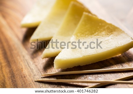 Spanish cheese sliced on wooden board with toothpicks. - stock photo