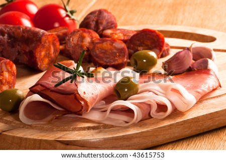 Spanish chorizo sausage with parma ham and olives garnished with rosemary herbs - stock photo