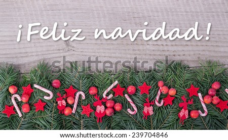spanish Christmas card with Pine green, candy Canes, apples and text Merry Christmas/Merry Christmas/spanish - stock photo