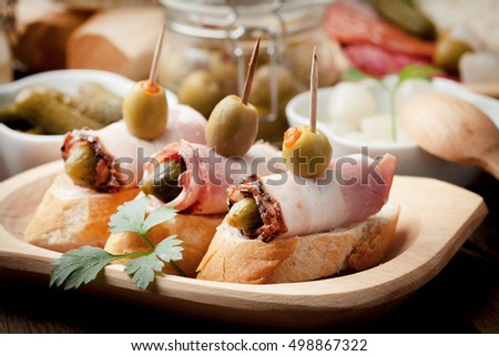 Spanish cuisine. Tapas with sliced bacon, olives and cucumber on a wooden table. on a wooden table.