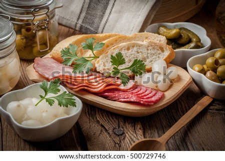 Spanish cuisine. Tapas with sliced sausage, salami, olives, marinated onions, cucumber and parsley on a wooden table.