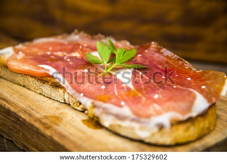 Spanish cured serrano ham with olive oil and toasted bread - stock photo