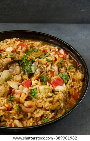 Spanish dish called paella with seafood, on the pan, grey background.