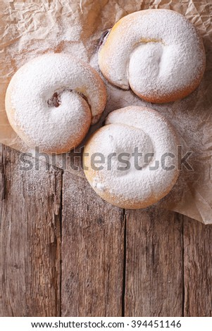Spanish ensaimada pastries with berries on the table. vertical view from above - stock photo