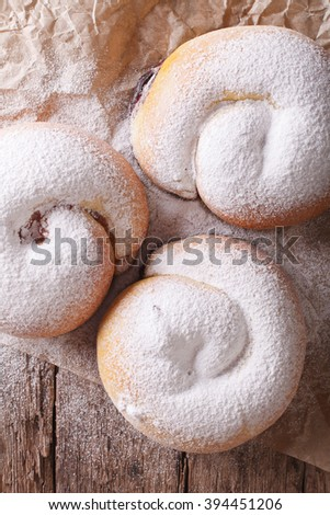 Spanish ensaimadas sweet rolls with powdered sugar close-up on the table. vertical view from above - stock photo