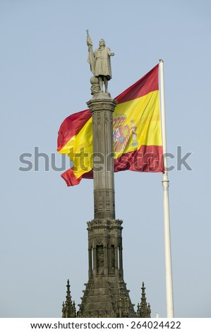 Spanish flag waves behind statue of Christopher Columbus, Plaza de Col�¢??n in Madrid, Spain