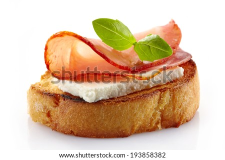 Spanish food tapas. Toast with fresh goat cheese and smoked serrano meat isolated on white - stock photo