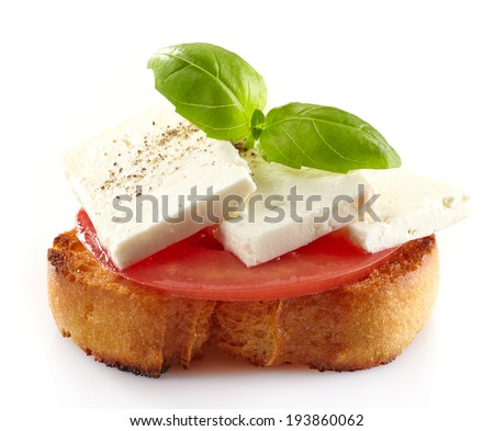 Spanish food tapas, Toast with fresh goat cheese, tomato and basil isolated on white - stock photo