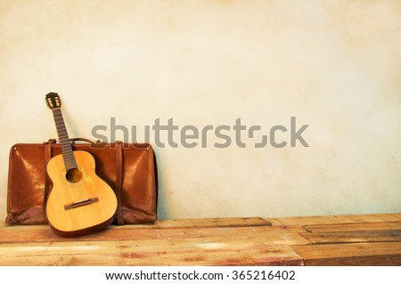 Spanish guitar  and suitcase propped in front of a white wall as background
