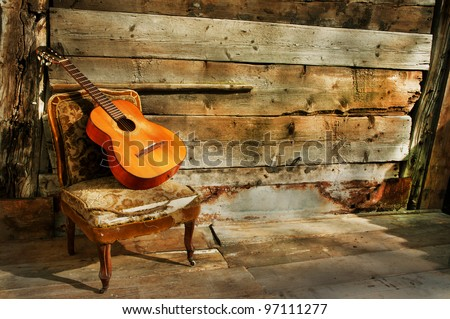 spanish guitar on a old chair with  wooden background horizontal - stock photo