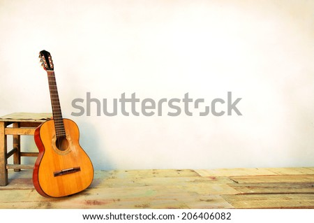 Spanish guitar propped in front of a white wall as background