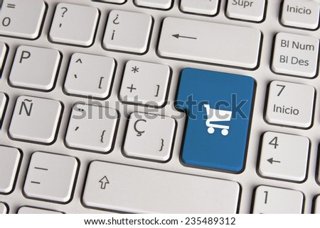 Spanish keyboard with buy shopping cart icon over blue background button. Image with clipping path for easy change the key color and editing. - stock photo