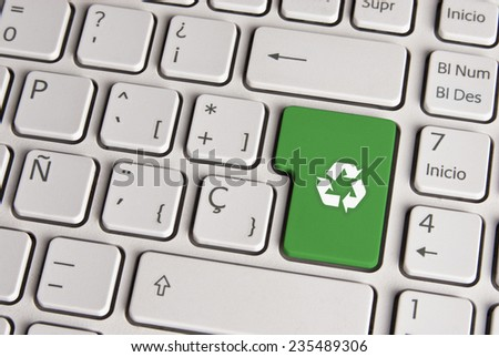 Spanish keyboard with ecology concept recycle symbol icon over green background button. Image with clipping path for easy change the key color and editing. - stock photo