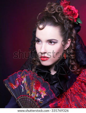 Spanish lady. Portrait of young woman in artistic image posing with fan