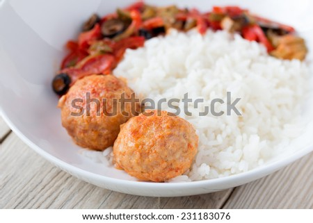 Spanish Meatballs albondigas with vegetables and cooked rice on wooden table - stock photo