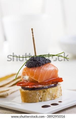 Spanish montadito tapa with salmon and caviar - stock photo