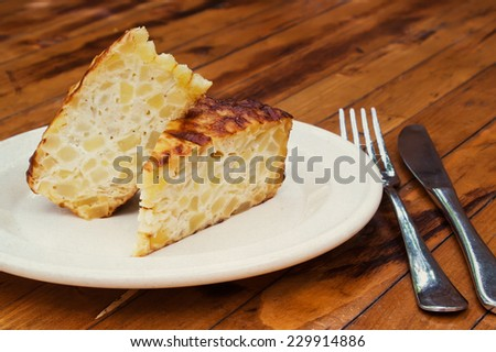 Spanish omelet on a white plate. The plate on the wooden table. Spanish omelette with potatoes and onion. Tortilla espanola (wooden table background). vintage paper background. - stock photo