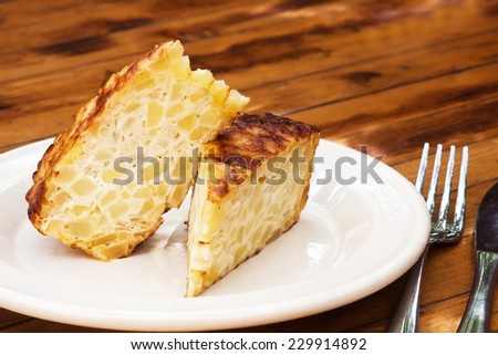 Spanish omelet on a white plate. The plate on the wooden table. Spanish omelette with potatoes and onion. Tortilla espanola (wooden table background). - stock photo
