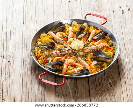 Spanish paella with shrimp and mussel in traditional pan on a old wooden table - stock photo