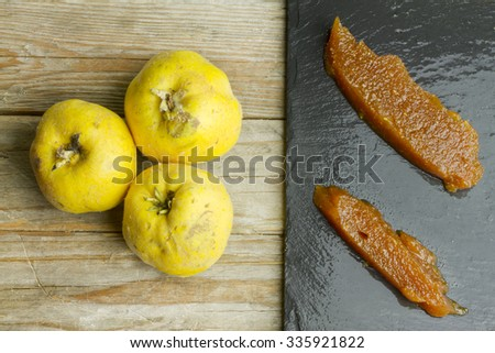 Spanish quince slices paste on a slate plate with three quince fruits on wooden background - stock photo