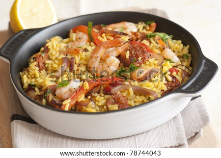 Spanish rice with king prawns and chorizo in a pan
