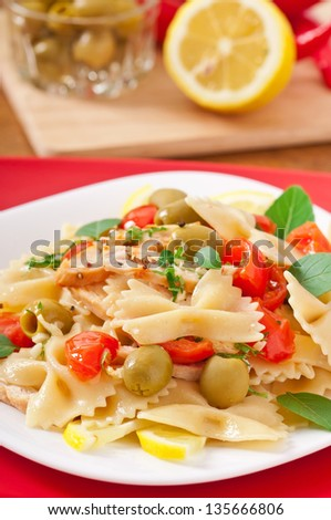 Spanish salad with pasta bows, tomatoes and chicken - stock photo