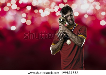 Spanish soccer player, celebrating the championship with a trophy in his hand. On a red lights background.