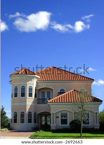 spanish style home against blue sky - stock photo
