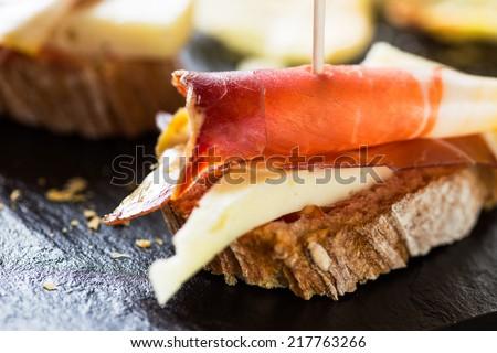 Spanish tapas: slice of bread, cheese and spanish ham. - stock photo