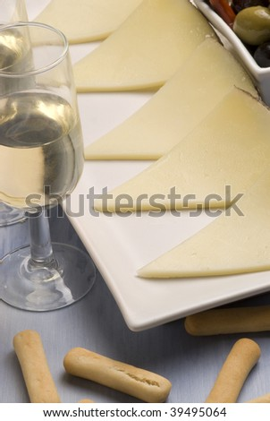 Spanish tapas. Sliced manchego cheese. Sherry wine. Typical appetizer. - stock photo