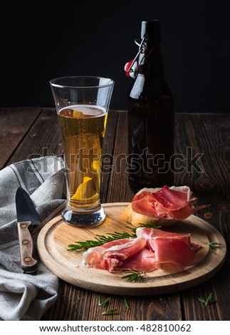 Spanish tapas with jamon, glass and bottle of beer on a wooden background