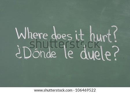 "Spanish to English translation for ""where does it hurt"" on chalkboard - stock photo"